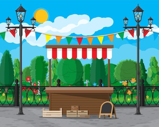 Stalla di legno vuota dell'alimento del mercato tradizionale con le bandiere, bordo di gesso delle casse parco cittadino, lampione e alberi. cielo con nuvole e sole. tempo libero nel parco cittadino estivo. stile piatto di illustrazione vettoriale