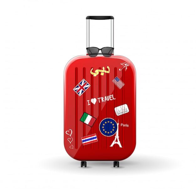Borsa da viaggio con adesivi. valigia rossa lucida con occhiali da sole in cima. viaggia nel mondo.