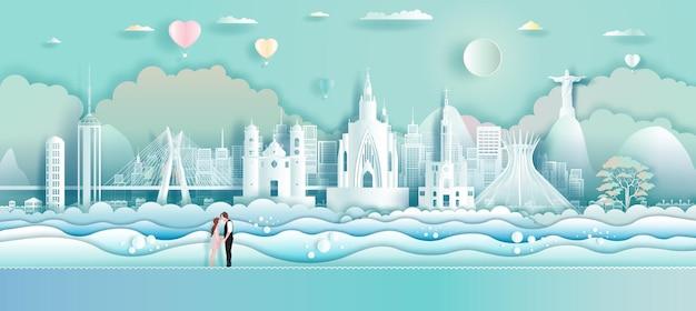 Viaggia verso i punti di riferimento del brasile in sud america con palloncini d'amore e coppia nell'arte della carta, origami, carta tagliata design. viaggia a rio de janeiro e tour brasil nell'architettura moderna dell'america. illustrazione vettoriale.