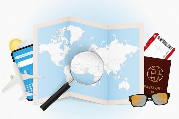 Destinazione di viaggio modello turistico del benin con attrezzatura da viaggio e mappa del mondo