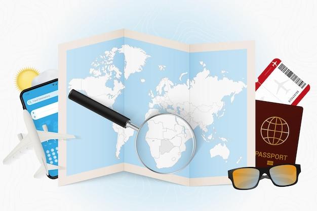 Destinazione di viaggio botswana, mockup turistico con attrezzatura da viaggio e mappa del mondo con lente d'ingrandimento su un botswana.