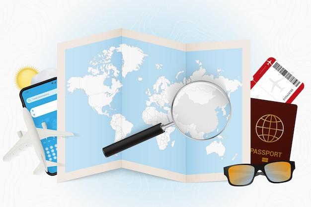 Destinazione di viaggio cina, modello turistico con attrezzatura da viaggio e mappa del mondo con lente d'ingrandimento su una cina.