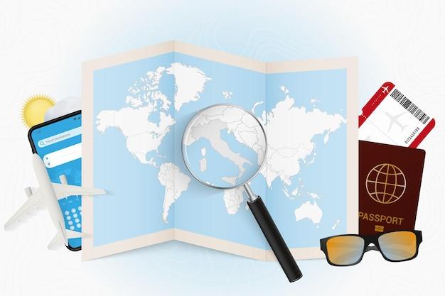 Destinazione di viaggio italia, mockup turistico con attrezzatura da viaggio e mappa del mondo con lente d'ingrandimento su un'italia.