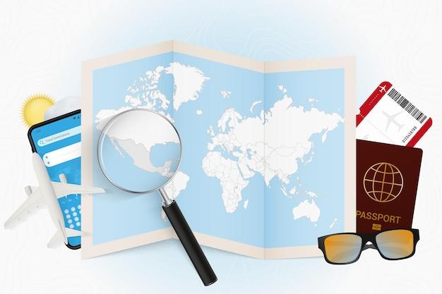 Destinazione di viaggio messico, modello turistico con attrezzatura da viaggio e mappa del mondo con lente d'ingrandimento su un messico.