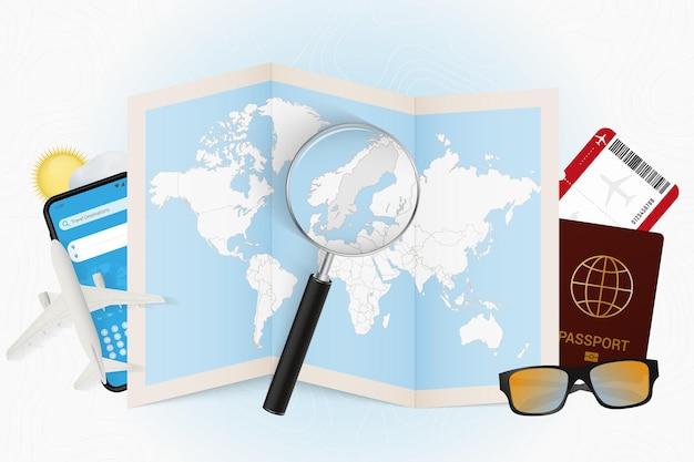 Destinazione di viaggio turismo svezia con attrezzatura da viaggio e mappa del mondo con lente d'ingrandimento