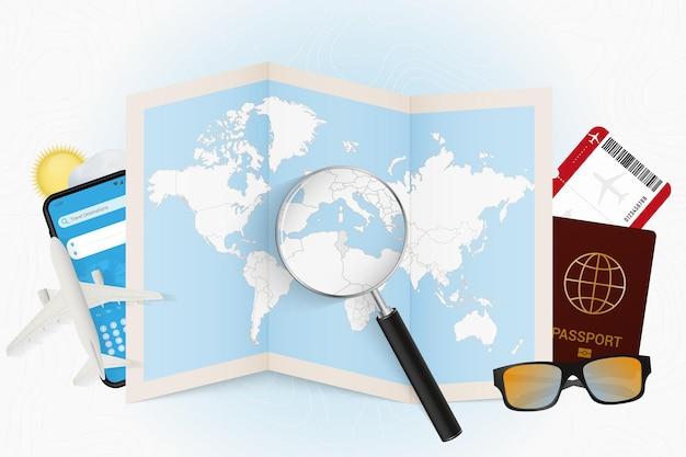 Destinazione di viaggio tunisia, modello turistico con attrezzatura da viaggio e mappa del mondo con lente d'ingrandimento su una tunisia.