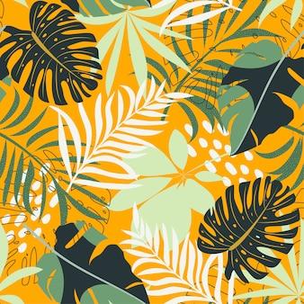 Tendenza del modello senza cuciture astratto con le foglie e le piante tropicali variopinte su giallo