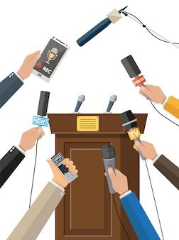 Tribuna e mani di giornalisti con microfoni