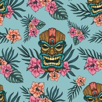 Modello tropicale senza cuciture con maschera tiki polinesiana e fiori di ibisco e foglie esotiche