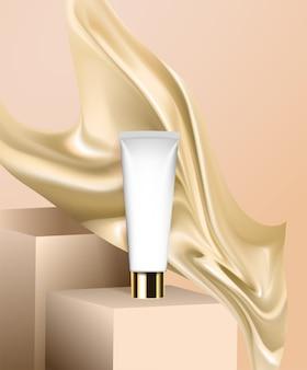 Un tubetto di crema è sul podio, stoffa e seta volano nelle vicinanze.