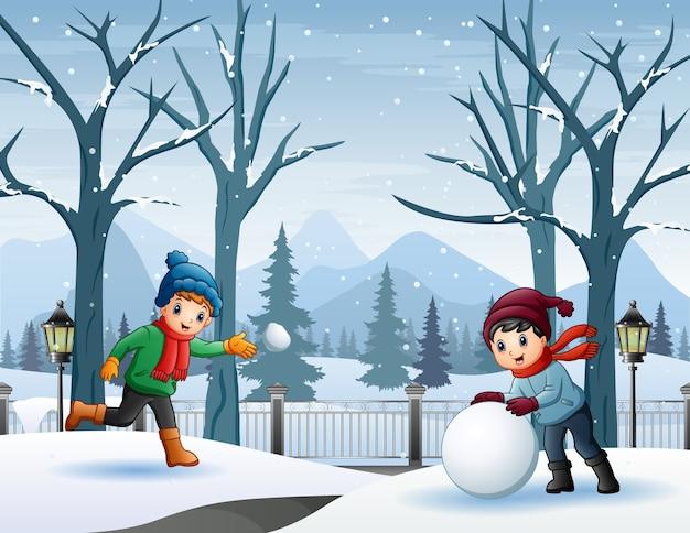 Due ragazzi che giocano a palle di neve nel parco innevato