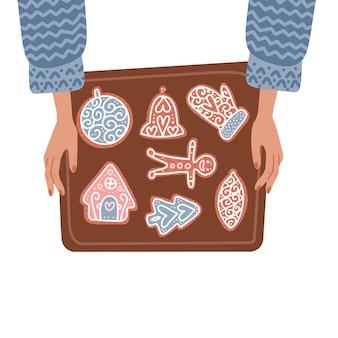 Due mani femminili che tengono la teglia con i biscotti di panpepato di natale vista dall'alto concetto isolato fl...