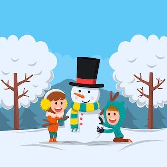 Due bambini felici che fanno pupazzo di neve