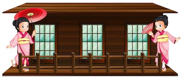 Due ragazze giapponesi alla capanna di legno