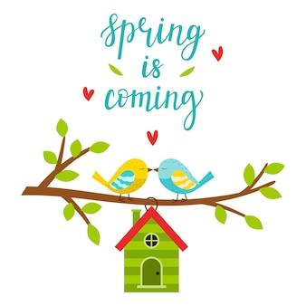 Due piccioncini su un ramo con foglie. una casetta per uccelli a forma di casa. scrivere la primavera sta arrivando