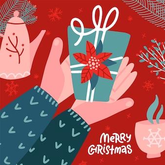 Due mani maschii che tengono il regalo della scatola, souvenir di natale, illustrazione di vettore piatto. il braccio dell'uomo dà il regalo del nuovo anno. scena hygge vista dall'alto con pentola, tazza e decorazioni floreali.