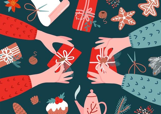 Due paia di mani e confezione regalo sul tavolo.
