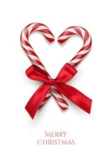 Due bastoncini di zucchero a strisce rosse a forma di cuore con fiocco rosso e testo di buon natale isolato su priorità bassa bianca.