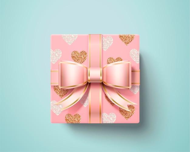 Confezione regalo di san valentino con fiocco in nastro rosa e carta da imballaggio a forma di cuore nell'angolo di vista dall'alto, stile 3d