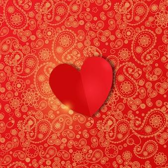 Sfondo di san valentino con cuore di carta su un bellissimo motivo paisley rosso.