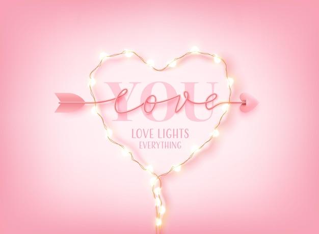 Biglietto o banner di san valentino con parola love you, luci a led a stringa e scritte disegnate a mano con parole scritte a mano di arrow sul rosa.