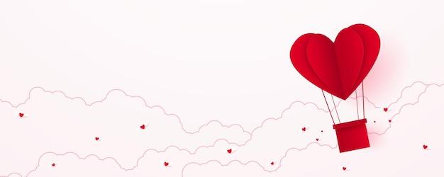 Il giorno di san valentino amore concetto carta sfondo rosso a forma di cuore mongolfiera che galleggia nel cielo