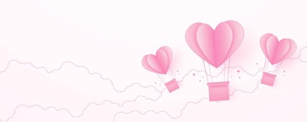 San valentino amore concetto sfondo carta rosa a forma di cuore mongolfiere che galleggiano nel cielo