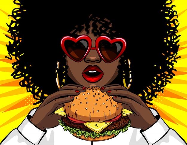 Donna afroamericana dell'insegna di vettore che mangia un hamburger. retro illustrazione di vettore di pop art comico del fumetto che disegna le mani femminili che tengono un panino squisito