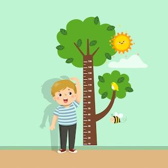 Vector il ragazzo sveglio del fumetto dell'illustrazione che misura la sua altezza con il grafico di altezza dell'albero sulla parete.