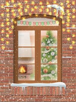Vista attraverso una finestra all'interno di un soggiorno di natale con l'albero di natale e il caminetto. la facciata in mattoni della casa decorata con ghirlande luminose.