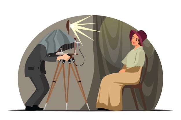 Fotografo vintage con fotocamera retrò. uomo che scatta fotografie con una modella sorridente in uno studio vecchio stile