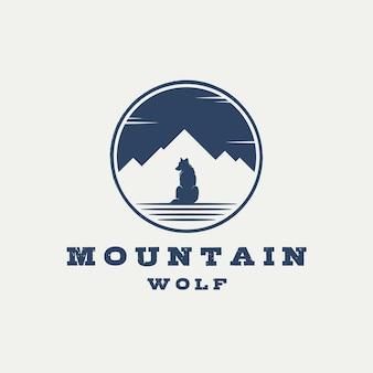 Emblema dell'etichetta distintivo retrò vintage logo lupo seduto con silhouette di montagna