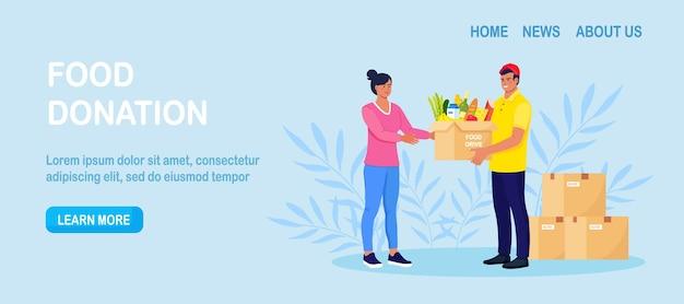 Volontariato in possesso di una scatola per le donazioni, pacchetto con generi alimentari. operatori umanitari che distribuiscono cibo alle persone bisognose. carità, donazione di cibo per bisognosi e poveri, senzatetto