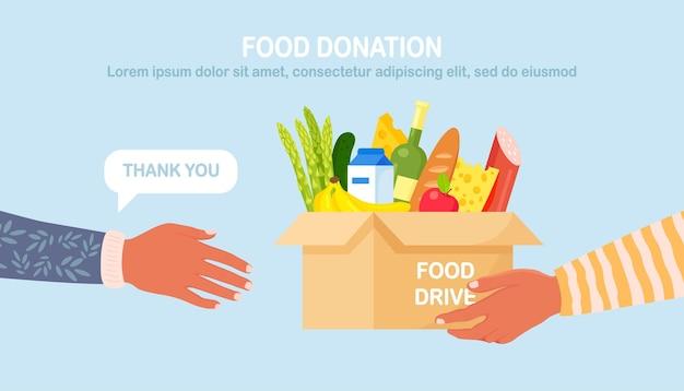 Volontario in possesso di una scatola di donazione con cibo per le persone affamate diversi prodotti alimentari per i senzatetto in rifugio. concetto di solidarietà e beneficenza