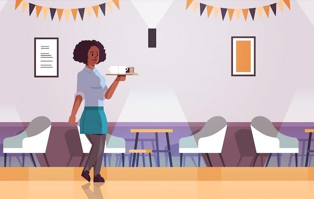 Cameriera portando caffè e torta sul vassoio