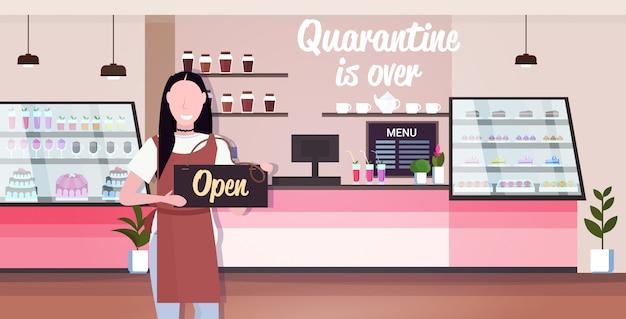La cameriera di bar con cartello aperto coronavirus quarantena sta concludendo la vittoria sul concetto