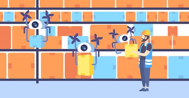 Lavoratore del magazzino che invia le scatole di cartone con i quadricotteri automatici di concetto della gestione logistica di servizio di consegna del fuco che volano con la scatola in orizzontale integrale del magazzino