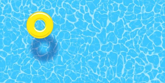 Fondo di estate della piscina di acqua con l'anello giallo del galleggiante della piscina.