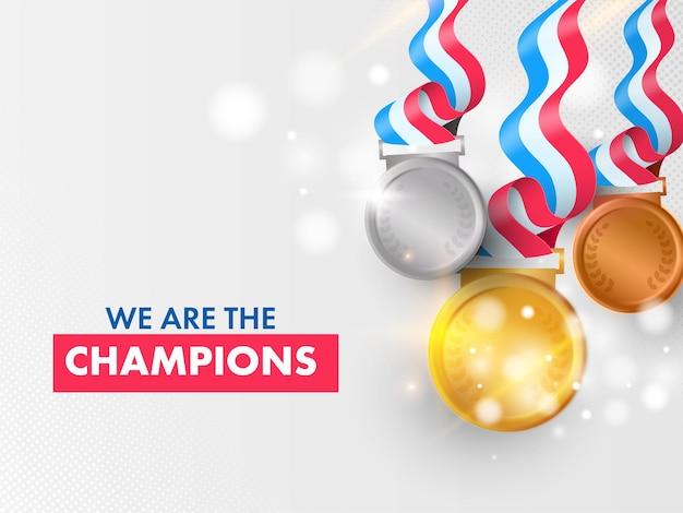 Design di poster basato su we are the champions con tre medaglie realistiche su bokeh grigio