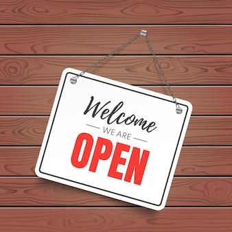 Benvenuto siamo superficie di legno aperta con cartello bianco. illustrazione