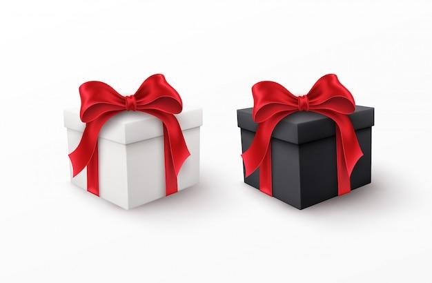 Contenitori di regalo bianchi e neri con gli archi di seta rossi isolati