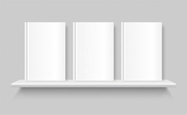 Libri in bianco bianchi su uno scaffale per libri. copertina vuota del libro. mensola sul muro grigio.