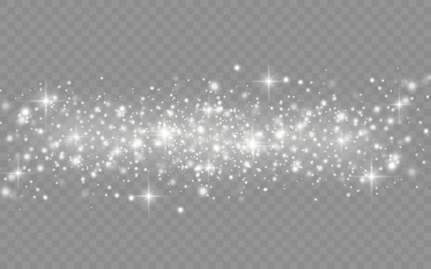 La polvere bianca scintilla e la stella brilla di luce speciale, effetto luce scintillante di natale, scintille, luci brillanti, particelle di polvere magica scintillante isolate su sfondo trasparente.