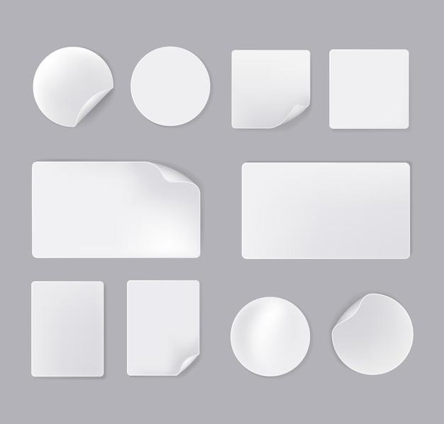 Insieme isolato adesivi di carta vuoti bianchi