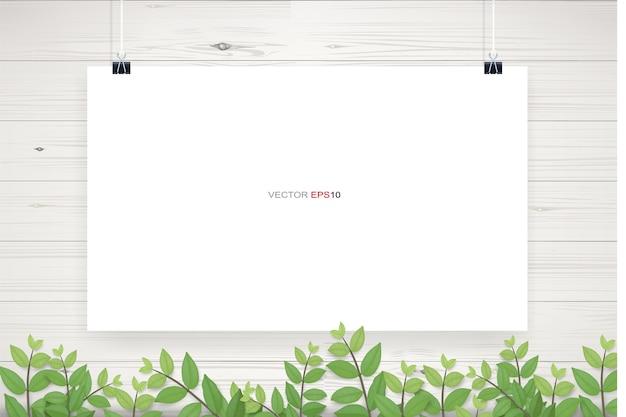 Poster di carta bianca appeso sul fondo di struttura della parete in legno bianco con cornice di foglie verdi
