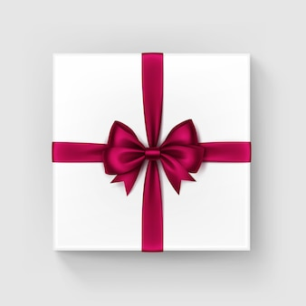 Scatola regalo quadrata bianca con fiocco in raso vinoso rosso bordeaux lucido e vista dall'alto del nastro vicino isolato su priorità bassa bianca