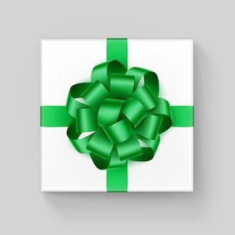 Scatola regalo quadrata bianca con fiocco in nastro verde smeraldo lucido vicino vista dall'alto isolato su sfondo