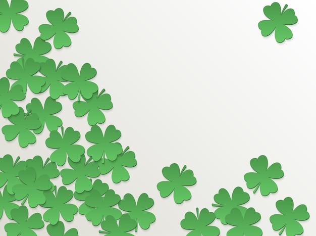 Fondo bianco di giorno di san patrizio con foglie tagliate di carta verde piatta a quattro foglie di trifoglio design semplice.