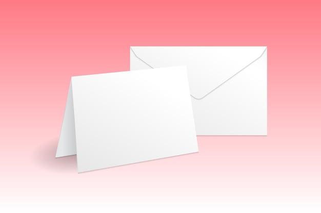 Modello di modello di biglietto di auguri e busta in piedi bianco isolato su sfondo rosa sfumato