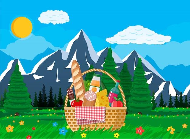 Cestino da picnic wicker pieno di prodotti e natura